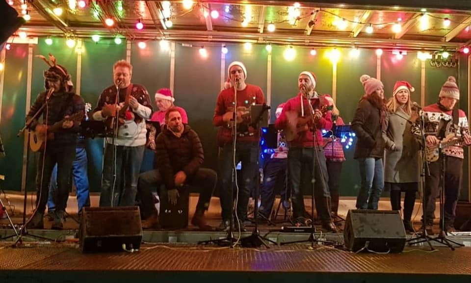 Alresford Ukulele Jam play to the crowd at The Arrival of Father Christmas in Broad Street